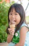 La fille asiatique mignonne mangent la crème glacée  Photographie stock