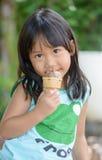 La fille asiatique mignonne mangent la crème glacée  Photographie stock libre de droits