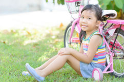 La fille asiatique mignonne s'asseyent près de la bicyclette photographie stock