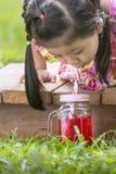 La fille asiatique mignonne sucent le nectar rouge doux dans le broc d'herbe Photo stock