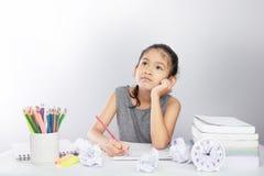 La fille asiatique obtiennent ennuyeuse sur son étude photo stock