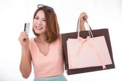 La fille asiatique ont plaisir à faire des emplettes avec la carte de crédit et l'isolant de panier Photos stock
