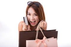 La fille asiatique ont plaisir à faire des emplettes avec la carte de crédit et le panier d'isolement sur le fond blanc Photos stock