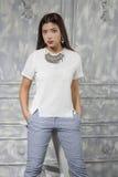 La fille asiatique s'est habillée dans une chemise blanche et des pantalons bleus photographie stock libre de droits