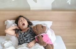 La fille asiatique se réveille et s'étirant sur le lit photo libre de droits