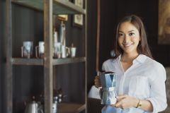 La fille asiatique se tenant tenante un sourire de pot de café et ont l'amusement vrai photo libre de droits