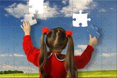 La fille assemblent le grand puzzle Photographie stock