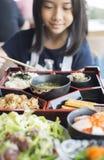 La fille assez asiatique apprécient la nourriture japonaise dans la gamelle de bento images stock