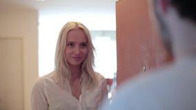 La fille assez blonde avec le sourire se tient à la porte ouverte, regarde l'homme qui l'étreint banque de vidéos