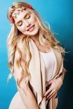 La fille assez blonde de jeunes avec les cheveux blonds bouclés et peu abaisse le sourire heureux sur le fond de ciel bleu Images stock