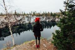 La fille assez gentille apprécient la belle vue de lac du hilltopl et le temps beau en Carélie Autour des roches Photos stock