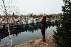La fille assez gentille apprécient la belle vue de lac du hilltopl et le temps beau en Carélie Autour des roches Image stock