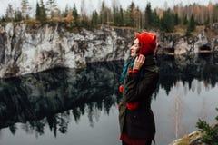 La fille assez gentille apprécient la belle vue de lac du hilltopl et le temps beau en Carélie Autour des roches Image libre de droits
