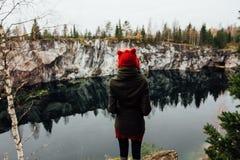 La fille assez gentille apprécient la belle vue de lac du hilltopl et le temps beau en Carélie Autour des roches Photographie stock