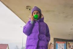 La fille assez jeune boit du café ou du thé, rue Images stock