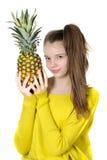 La fille assez jeune tient un grand ananas Image libre de droits