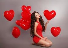 La fille assez mignonne de brune en rouge avec le coeur monte en ballon posant l'isolant Photos libres de droits