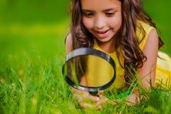 La fille assez petite avec la loupe regarde l'herbe Photos stock
