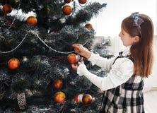 La fille assez petite décorent le grand arbre de Noël Photos libres de droits