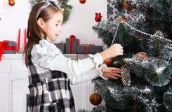 La fille assez petite décorent le grand arbre de Noël Photos stock