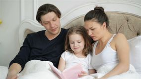 La fille assez petite essaye de lire avec ses parents se trouvant sur le lit Le bel enfant lit la représentation par le doigt banque de vidéos