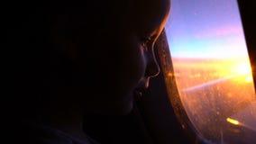 La fille assez petite regarde dans la fenêtre d'avion banque de vidéos