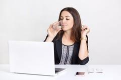La fille assoiffée boit l'eau du verre, ordinateur portable d'utilisations pour bloguer dans les réseaux, film de montres, relié  image stock
