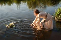 La fille attirante abaisse la guirlande dans l'eau photos libres de droits