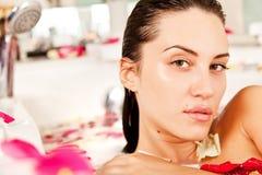 La fille attirante apprécie un bain avec du lait et des roses image stock