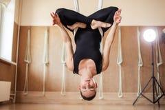 La fille attirante d'ajustement est accrocher à l'envers pendant la séance d'entraînement de yoga image libre de droits