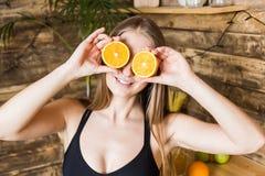La fille attirante dans les v?tements de sport a l'amusement, mettant des moiti?s d'orange ? ses yeux Les avantages de la consomm photo stock