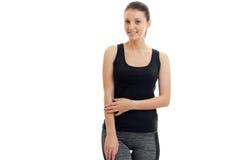 La fille attirante de sourire se tient dans un T-shirt noir et des pantalons et regarder l'appareil-photo images libres de droits