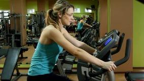 La fille attirante et sportive fait un cycle dans le gymnase de forme physique banque de vidéos