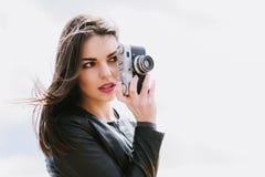 La fille attirante prend des photos avec un vieil appareil-photo image stock