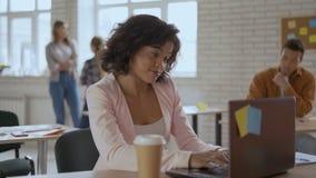 La fille attirante regarde soigneusement dans l'ordinateur attendant le message la fille régénère la page et les bâillements 4K banque de vidéos