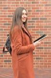 La fille attirante se tient dans la perspective d'un mur de briques photo libre de droits