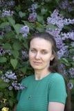 La fille attirante se tient prêt près des buissons du lilas violet Photographie stock