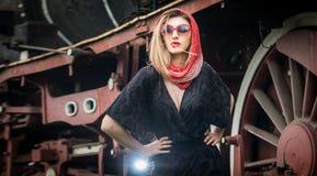 La fille attirante sexy avec les verres principaux rouges d'écharpe et de soleil posant sur la plate-forme devant un vintage s'ex Image stock