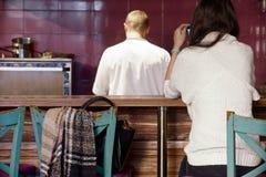 La fille attirante utilisent son téléphone au compteur de barre dans le café avec le cuisinier, qui a fait cuire les plats comman photo stock