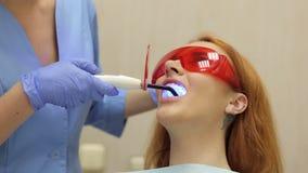La fille au dentiste, docteur de dentiste brille avec un émetteur à rayonnement ultraviolet sur ses dents banque de vidéos