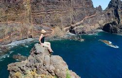 La fille au sommet de la roche s'assied et regarde des roches et Image libre de droits