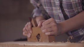 La fille au travail dans un atelier de menuiserie, avec une planeuse de main Plan rapproché banque de vidéos