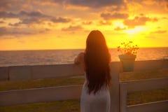 la fille aux cheveux foncés avec la figure chic a mis ses mains sur une barrière avec un pot de fleur, une dame dans la robe blan images stock
