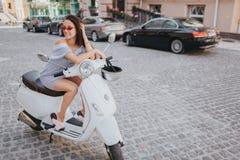 La fille aux cheveux foncés magnifique s'assied sur la moto et se penche là-dessus Elle tient une main près de la tête Elle est Photos libres de droits