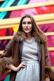 La fille aux cheveux longs ? la mode habill?e dans une robe grise et un long manteau de peau de mouton brun pose dans la rue images libres de droits