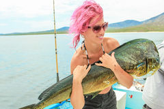 La fille aux cheveux roses de baudroie tient un poisson Dorado Photo libre de droits