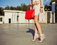 La fille aux longues jambes de mode et de style se tient en parc une soirée d'été dans une robe et une exploitation blanches cour Photo libre de droits