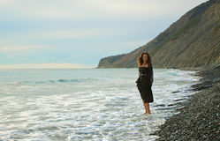 La fille aux pieds nus va le long du bord de la mer images stock