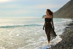 La fille aux pieds nus va le long du bord de la mer Photographie stock