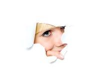 La fille avec émotion regarde par le papier déchiré Image stock